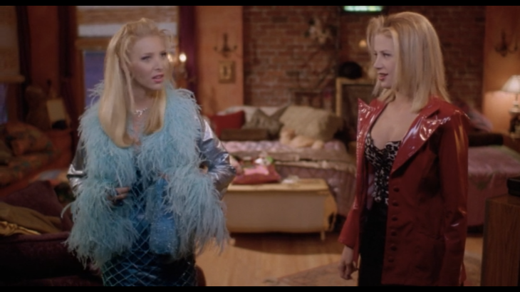 Two women in crazy outfits (Michele in a blue feather boa, Romy in a red patent coat and leopard corset) look happy.