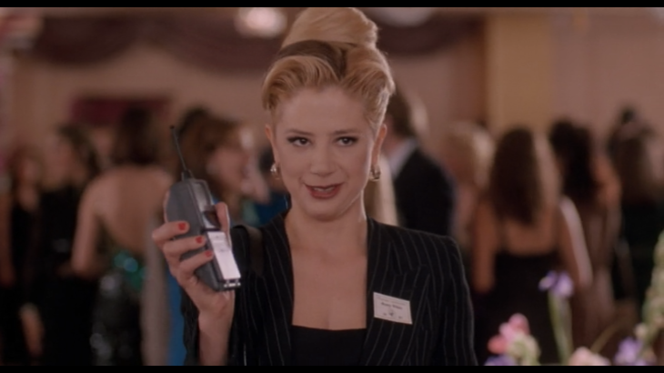 Romy holds up a giant 90s flip phone.
