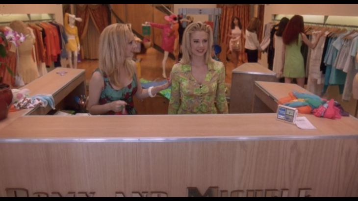 Two blonde women (Romy and Michele) behind a store counter clothes behind them.