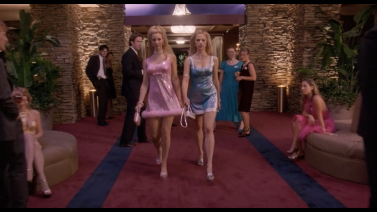 Two women in matching dresses, one pink (Michele), one blue (Romy), walk down a hallway looking fierce.