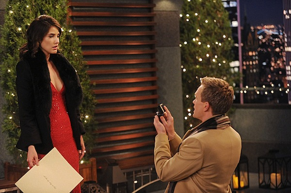 Barney kneels before Robin holding a ring while she wears a fancy dress and holds a giant piece of paper.