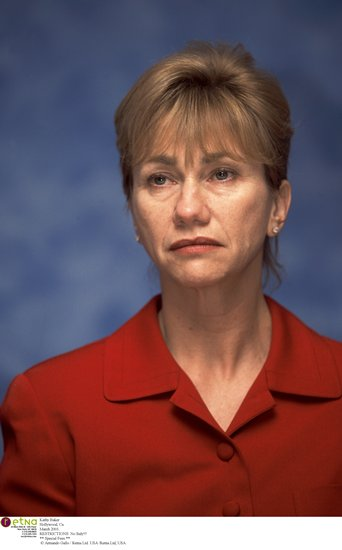 Kathy Baker, a white middle-aged woman, in a red suit on a blue background.