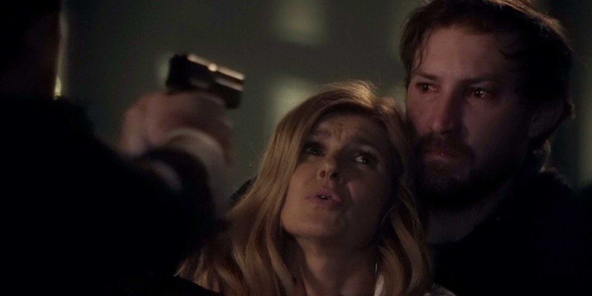 Rayna looks freaked out while an angry man behind her holds onto her and a gun points towards them both.