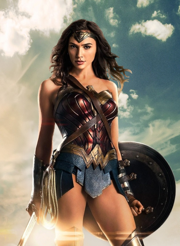 Wonder Woman holds a shield in one hand and a sword in the other, with a gleam of sun behind her.