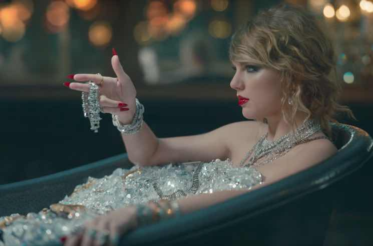 "Screenshot from ""Look What You Made Me Do"" music video - Taylor Swift sits in bathtub, covered in diamonds, pointing fingers like a gun."