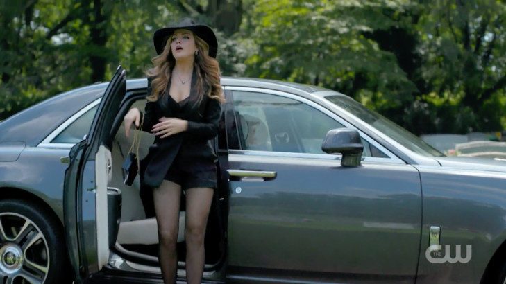 Fallon emerges from a car wearing black satin hot pants, a satin jacket, ab lack purse, a giant black hat, and sheer black tights.