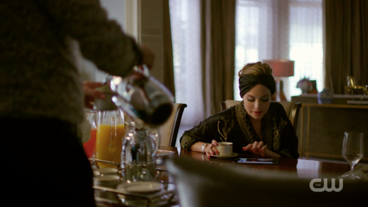 Fallon sits at the table with a tablet and a coffee mug, wearing a turban.