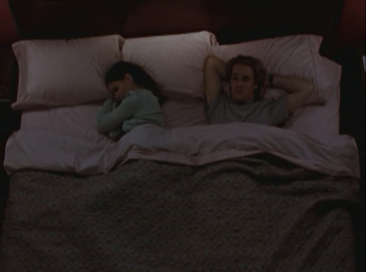 Joey and Dawson lie in a queen-sized bed, Joey facing away from Dawson on her side, Dawson with his hands clasped behind his head and his hair looking very ... tall.
