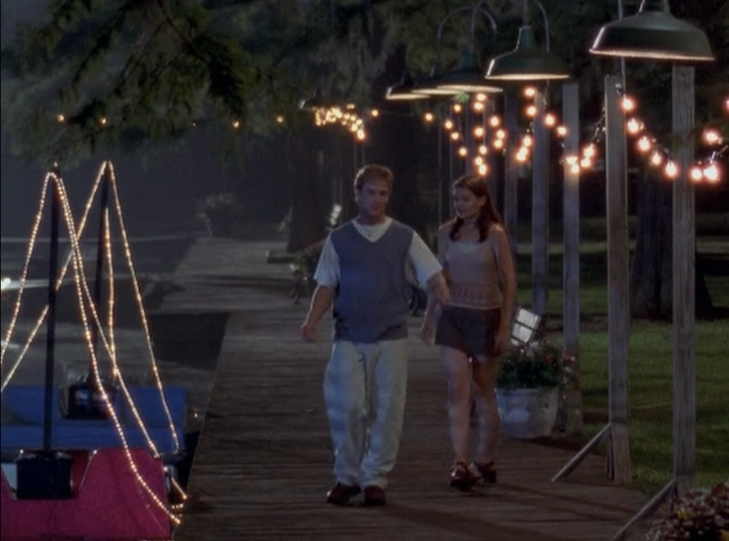 Joey and Dawson walk down a pier strewn with twinkle lights. Joey wears a pink tank top and a camo-green skirt, Dawson wears a giant shirt, a sweater vest, large white chinos, and a necklace.