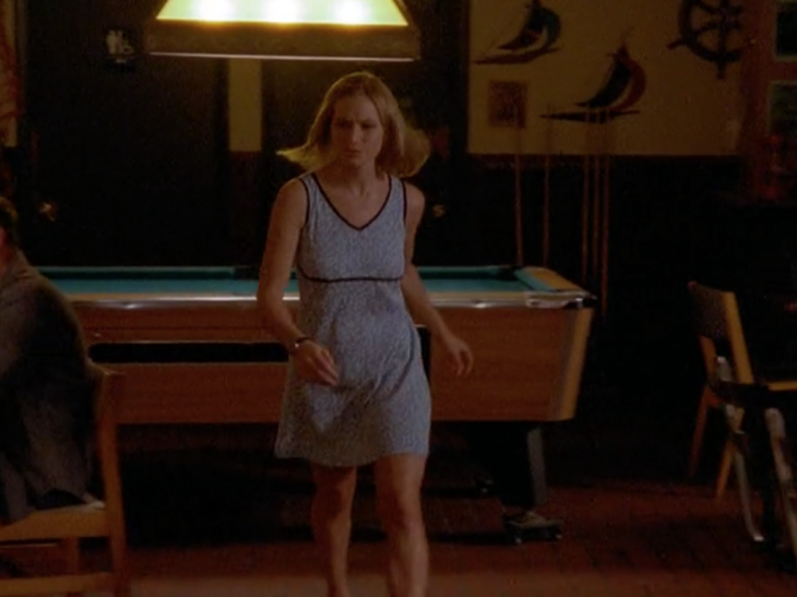 Andie walks in front of a pool table wearing a lavendar dress with contrasting black piping on the neckline, the armholes, and the horizontal line about three-fourths of the way down across her boobs.