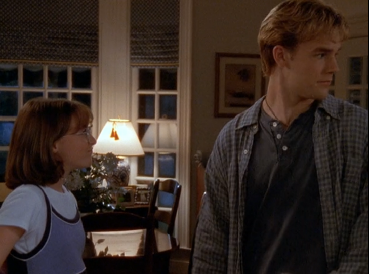 Dawson looks behind him, looking nervous, while a little girl looks up at him.