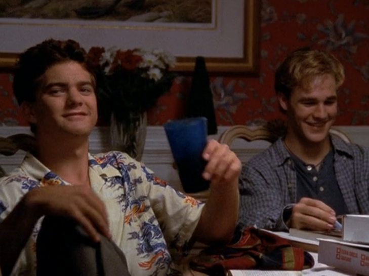 Pacey smirks while holding a cup of water, Dawson is laughing behind him.