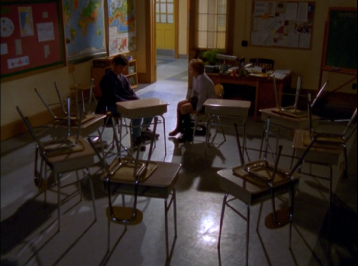 Jen and Jack sit facing each other in an empty, darkened classroom.
