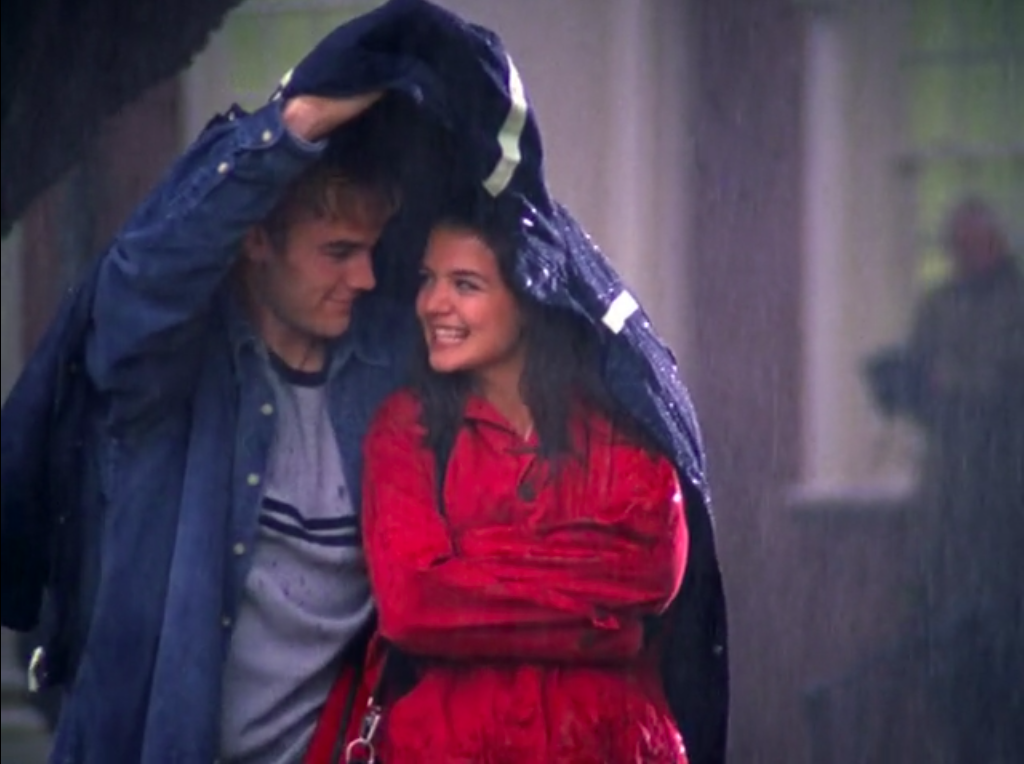 Joey and Dawson smile at each other under his coat while the rain comes down.