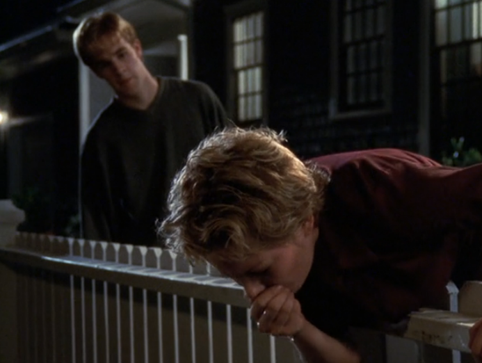 Image: Jen throwing up on a white picket fence while Dawson watches