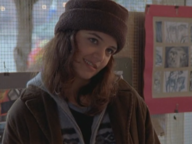 Joey wears a super cute brown hat, standing in front of her drawings.