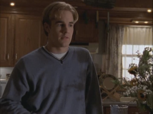 Dawson stands in his kitchen with symmetrical bangs going off to each side of his forehead.