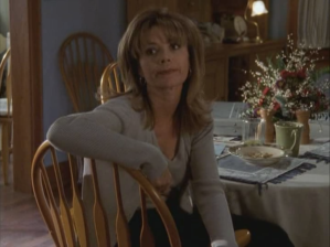 Gail sits in her kitchen with wispy bangs below her bouffant.