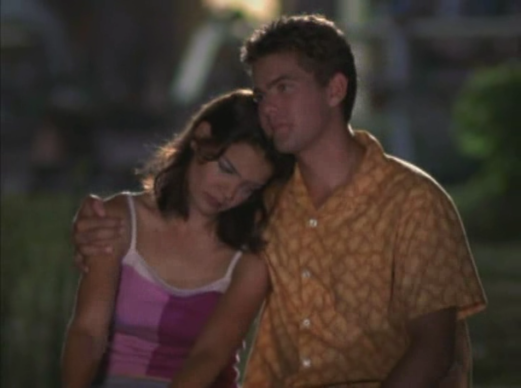 Pacey puts his arm around Joey as a crying Joey leans her head on his shoulder. Dark/exterior shot.