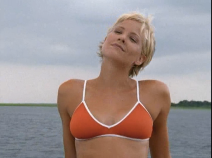 Eve leans back, open water behind her, wearing a red bikini top with white piping.