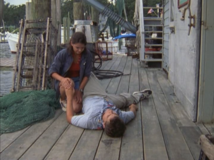 At the dock, Joey kneels over Pacey. He is lying flat on his back, patting her knee while she pats his hand.