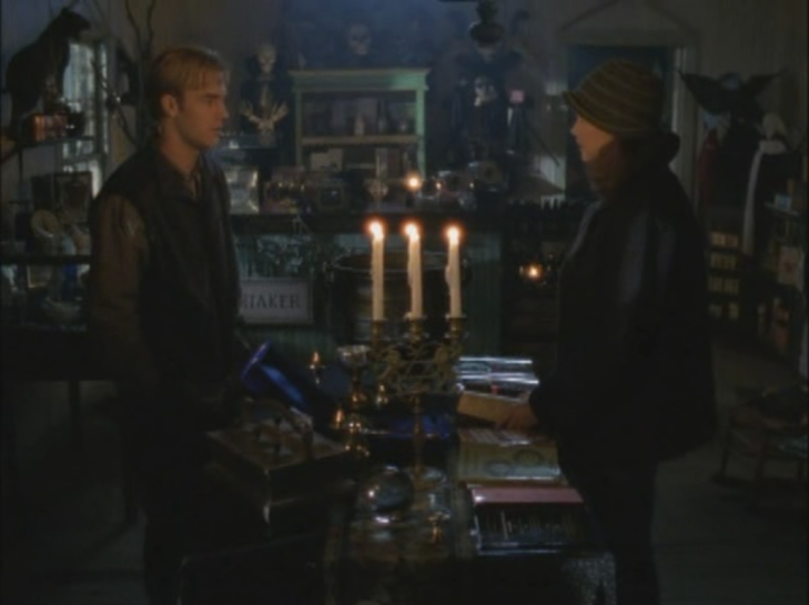 Joey and Dawson face each other in a shop, candles lit between them.