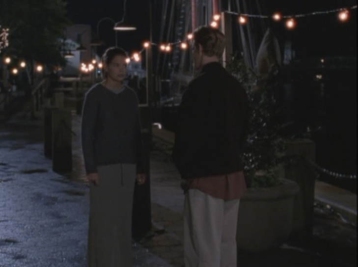 Joey and Dawson face each other on the dock, strung with twinkle lights. Joey wears a loose long sleeved sweater whose neckline barely goes below her collarbone in a dark grey-blue, and a long shapeless skirt in dark grey-green.