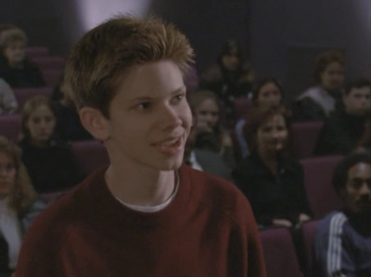 Shot of an actor who was on Boy Meets World standing in an auditorium in the audience, surrounded by a bunch of people.