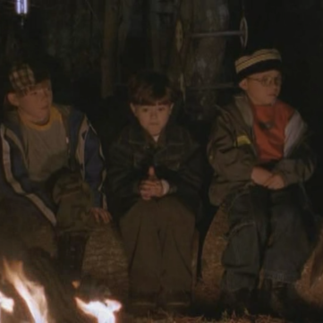 Three boys sitting on a log by a campfire. Right is Buzz, looking scared. Left is another kid looking a little nervous. In the center one kid stares straight ahead, his eyes wide.