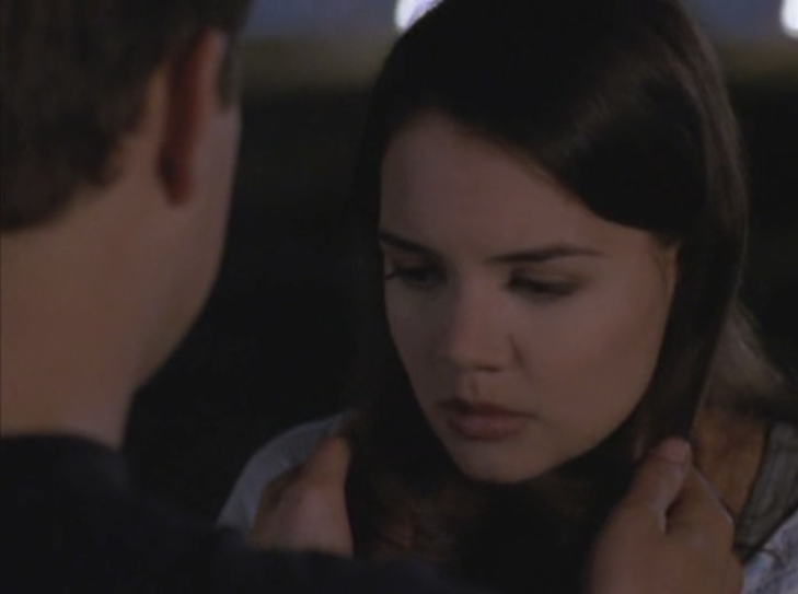 Joey looks down, looking sad, and Pacey (facing away from camera) tugs gently on her hair.