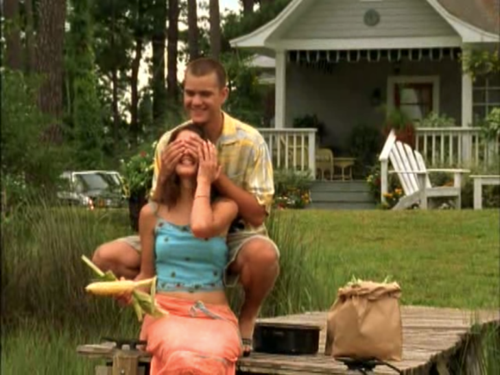 Out at the dock. Pacey kneels behind Joey grinning and covering her eyes with his hands. She's holding an ear of corn in one hand and holding his hand in the other, also grinning.