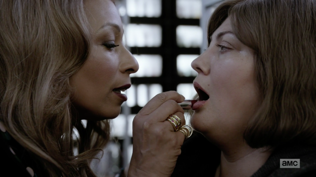 A white woman (right) with plain makeup and hair opens her mouth as a pretty, well-coifed black woman (left) leans in and presses a red lipstick to her lower lip.