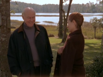 Exterior, day. Mr. Brooks and Grams stand in the yard. Brooks is wearing a coat over a wide-ribbed blue turtleneck sweater.
