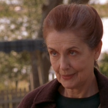 Closeup of Grams, smirking and lifting her eyebrows.