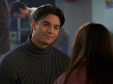 Drue, wearing a gray ribbed turtleneck.