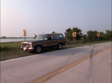 A car pulls off by the side of the road, near a field and a bunch of yellow warning signs for a curve.