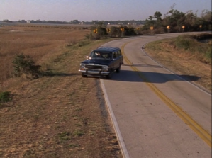 A car pulls off the side of the road. Fields are seen on the left side, and yellow signs warning of a curve in the road behind.