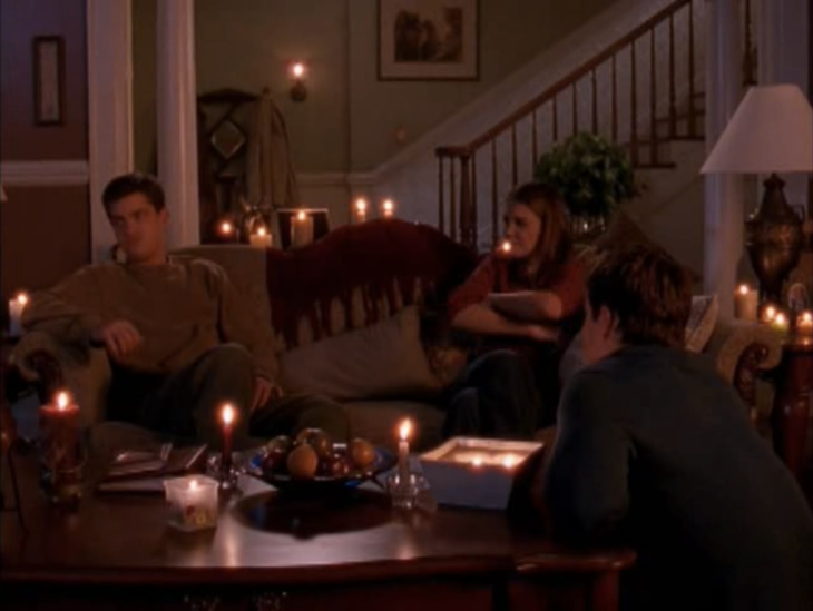 Long shot of three people - two brunette white men (Jack, at the coffee table; Pacey, on the couch on the left) one brunette white woman (Joey, on the couch, right) -- in a living room surrounded by candles.