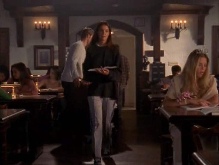 Joey (brunette white woman) walks through the library past a blonde white woman (Audrey) in a tiara. She is wearing gray sweatpants that are pleated.