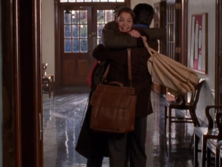 Long shot of Joey hgging her professor, both their bags swinging.