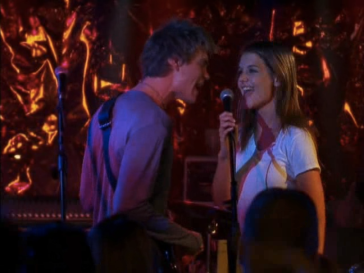 On stage, a young white woman with brown hair (Joey, right) holds the mic, singing towards a young white man with blonde hair (Charlie, left) and a guitar.