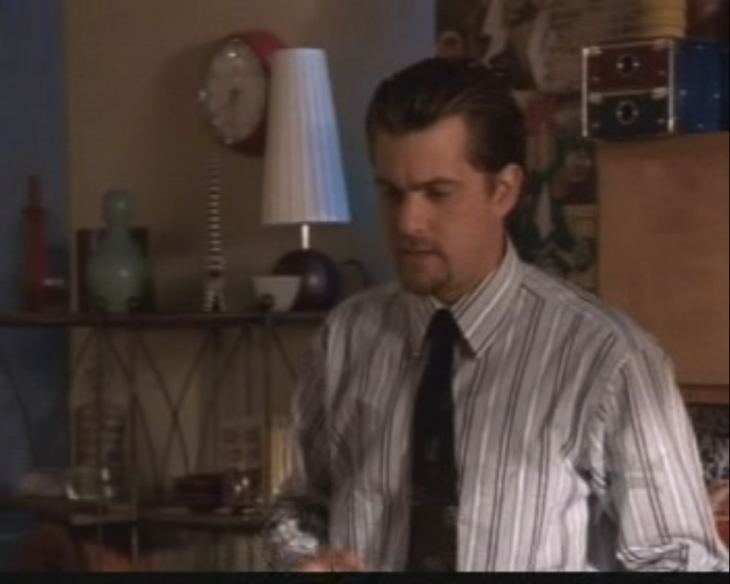 Pacey with greased-back hair, in a shirt and tie.