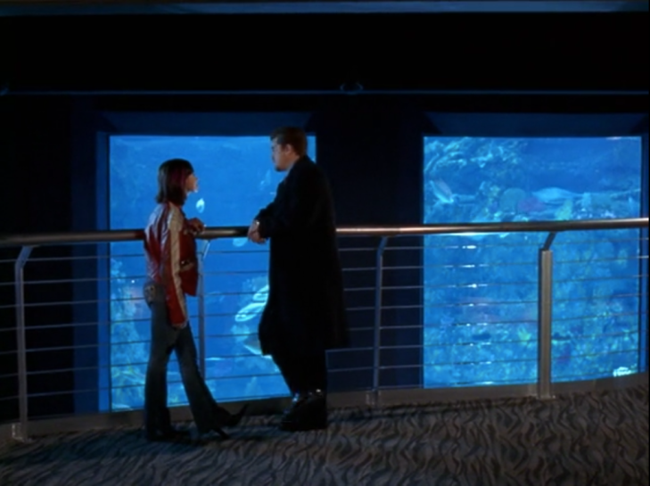 Pacey and Emma stand at a railing on the mezzanine of an aquarium, with blue aquarium windows in the background.