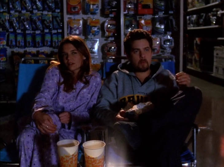 Joey and Pacey, wearing pajamas and sweatshirt respectively, are seen sitting on lawn chairs in a darkened store. Large soda cups in front of them. Pacey is chewing.