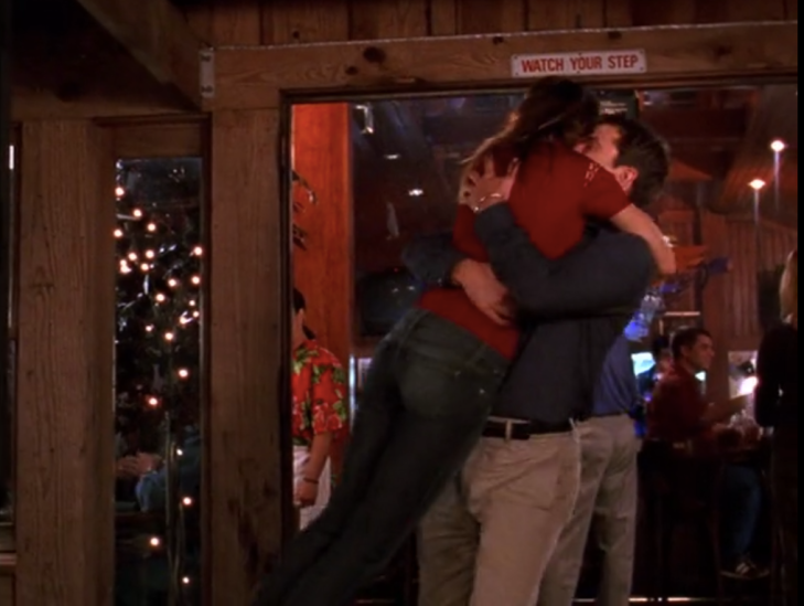 Pacey picks up Joey and holds her around the torso, mid-spinning her around.
