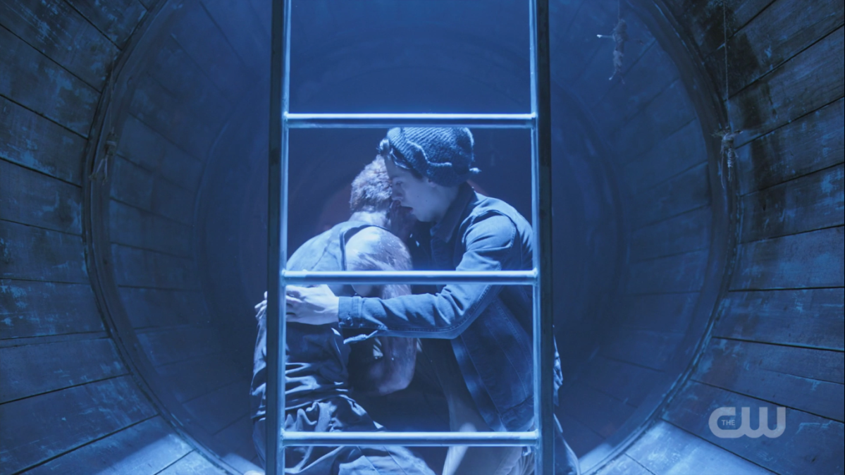 Behind a ladder inside a tunnel, Jughead hugs a battered-looking Archie.