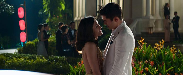 Outside in a lush garden outside a large house, a young woman in a formal dress stares lovingly up at a handsome man in a dinner jacket.