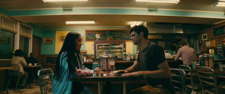 A teenaged girl and boy sit at a nearly-empty diner, facing each other across the table.