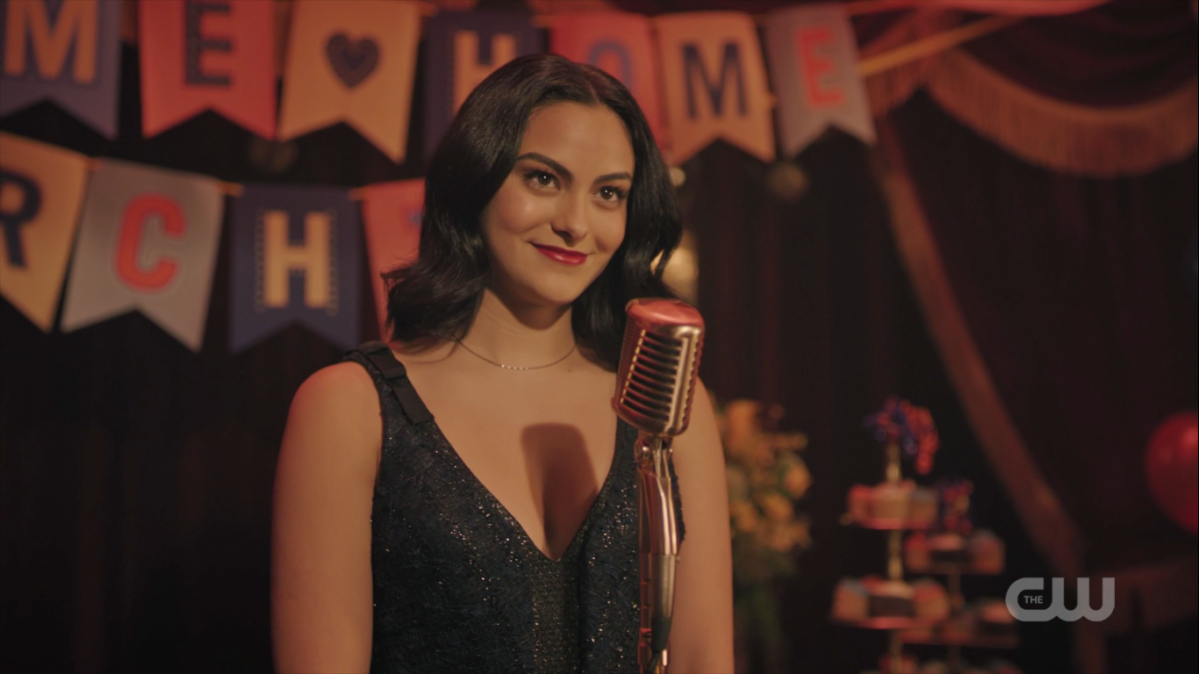 Veronica stands in front of a microphone in a sparkly dress, smiling.