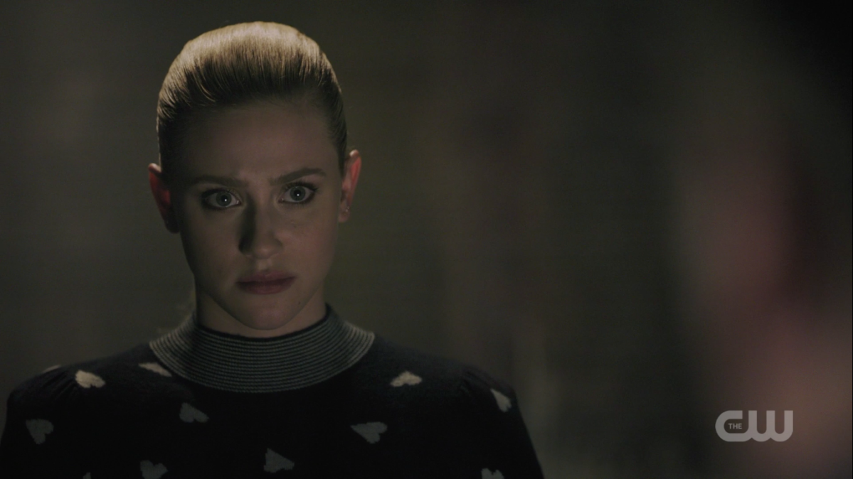 Betty, wearing a sweater covered in hearts at the jail, looks intensely forward.
